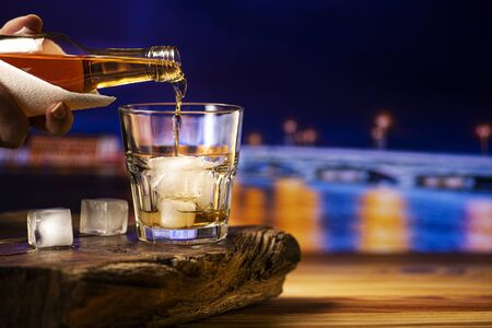 Pouring whiskey into a glass with ice. A glass of alcoholic beverage on a wooden table. 版權商用圖片