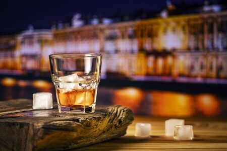 A glass of alcoholic beverage on a wooden table against the background of the night city. Whiskey cocktail with ice