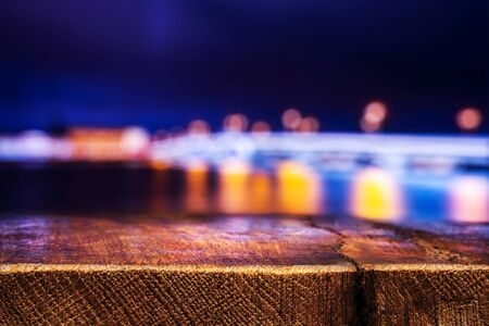 Empty Wooden Table with a View of Blurry Evening City. Backdrop for Product Placement