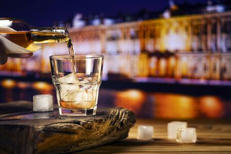 Pouring whiskey into a glass with ice against the background of the night city. A glass of alcoholic beverage on a wooden table. 版權商用圖片