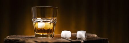 Un bicchiere di bevanda alcolica su un tavolo di legno. Cocktail di whisky con ghiaccio Archivio Fotografico