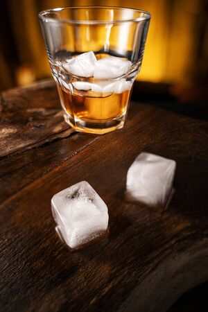 A glass of alcoholic beverage on a wooden table. Whiskey cocktail with ice top view