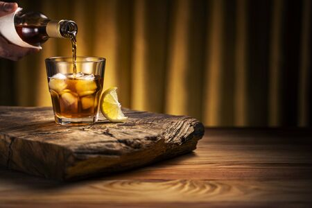 Pouring whiskey into a glass with ice. A glass of alcoholic beverage on a wooden table with a slice of lemon.