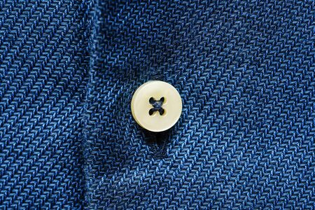 Blue shirt fabric with button. Textile background