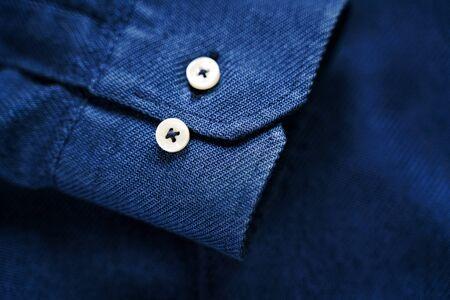 Niebieski rękaw koszuli z guzikami. Niebieska tekstura tkaniny. Krawiec tło