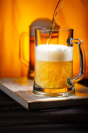Pour Light Beer into Mugs. Light Beer Glass Mugs with White Foam on Woowen Table and Yellow Background
