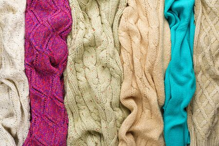 Several Different Colorful Knitted Sweaters Lays Side by Side as Background