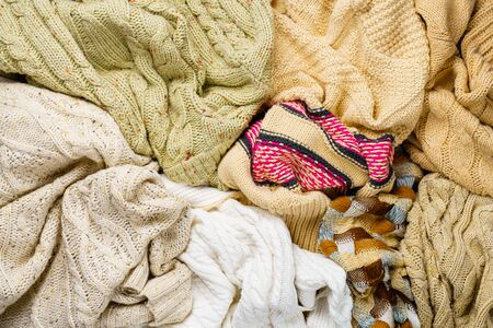 Many Knitted Winter Sweaters Piled in a Heap. Abstract Background of Winter Clothing