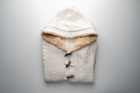 White hooded sweater with fur lining on white view from above