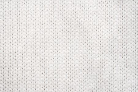 Sfondo di tessuto a maglia bianco. Trama di maglione di lana da vicino Archivio Fotografico