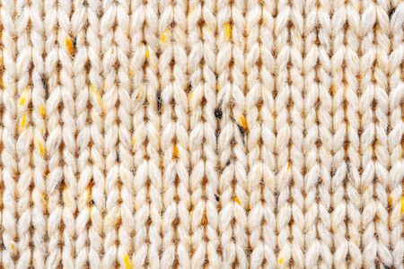 Texture of Wool Knit Beige Fabric Interspersed with Yellow Yarn. Sweater Background Close-Up View