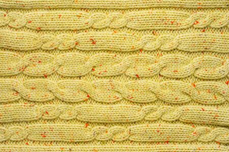 Texture of Wool Knit Color of Mustard Fabric Interspersed with Red Orange Yarn. Sweater Background Close-Up View