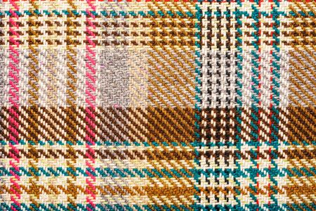 Brown checkered fabric with colored threads. Scottish wool. Fabric for plaid coat and suit. Close-up. Background