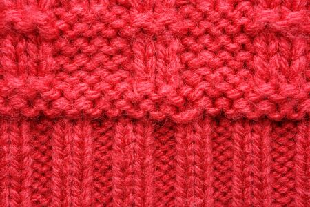 The texture of a knitted sweater. Red pattern. Facial surface. Background. Copy space