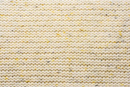 The texture of a knitted sweater. Beige pattern. Inside. Background. Copy space