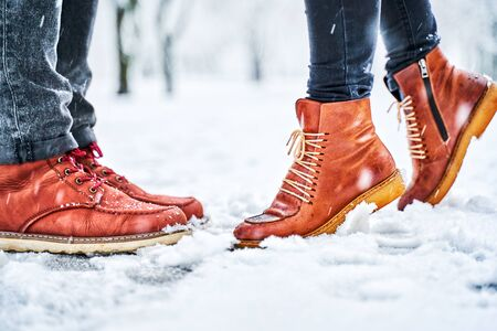 Feet of a couple on a snowy sidewalk in brown boots. Girl stands on toes while kissing. Winter weather concept Stock fotó