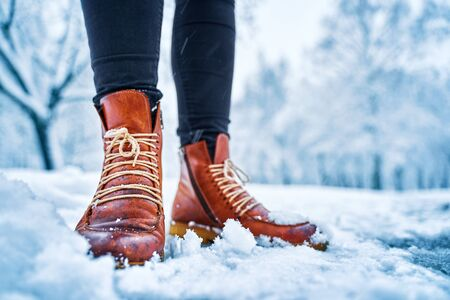 Feet of a woman on a snowy sidewalk in brown boots. Winter slippery pawement. Seasonal weather concept