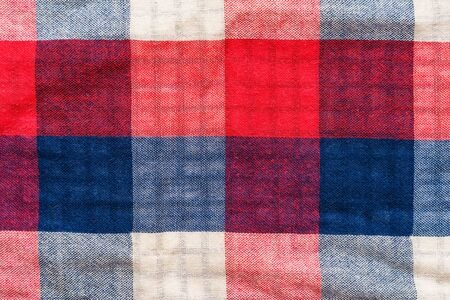 Plaid material texture. Red, blue and white cage clothes background