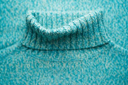 Blue turquoise sweater with a high collar. Winter clothes background