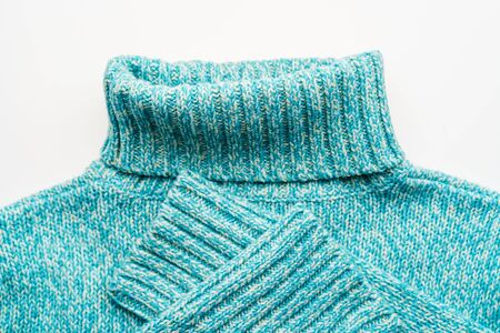 Blue turquoise sweater with a high collar on a white background.
