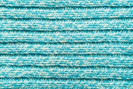 The texture of a blue turquoise knitted fabric. Sweater background
