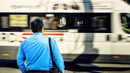 A man in a blue shirt in the bustle of the city against the backdrop of a passing bus. Man near the road view from the back. Tired man returns from office work. Work routine concept.