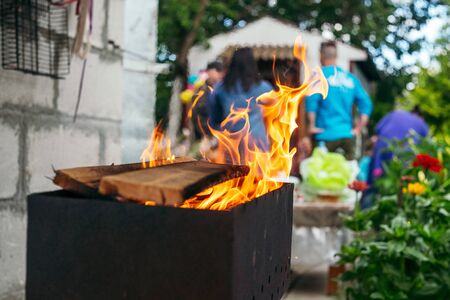 B-B-Q outdoors background. Kindling wood barbecue outdoors with open flame against the background of a group of people Stok Fotoğraf