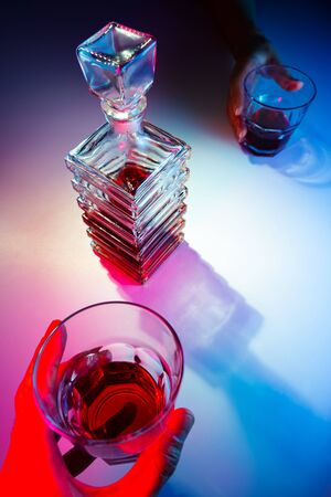 Glass square carafe with liquor with two glass glasses. Two people drink alcohol view from above
