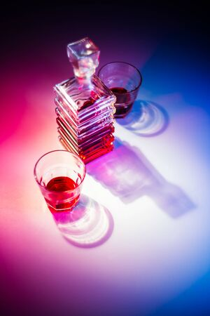 Glass square carafe with liquor with two glass glasses. View from above