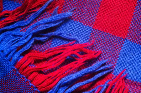Blue and red checked scarf with fringe as background