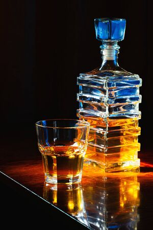 Glass of whiskey with old square carafe on a varnished wooden table Banque d'images - 143800278
