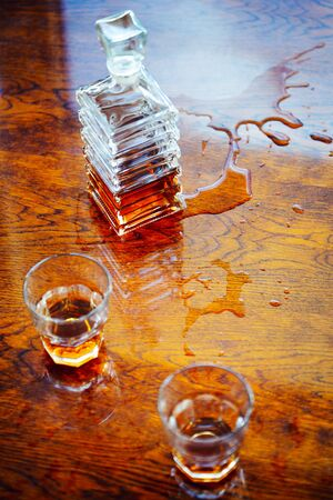 Whiskey old square carafe with two glasses on a varnished table top view