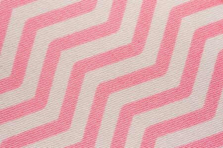 Pattern of pink and white striped zig zag. Macro textile texture