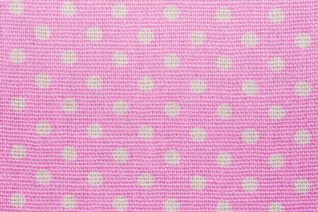 Pink and white spot pattern can be used for background. Polka dot macro texture of textile