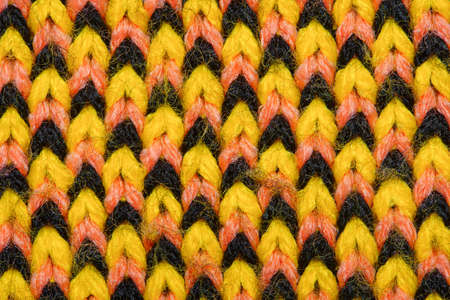 Yellow, red and black synthetic knitted fabric texture