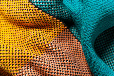 A pile of multi-colored knitted fabrics