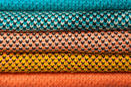 Stack of colorful knitted fabric, knitted winter clothes.
