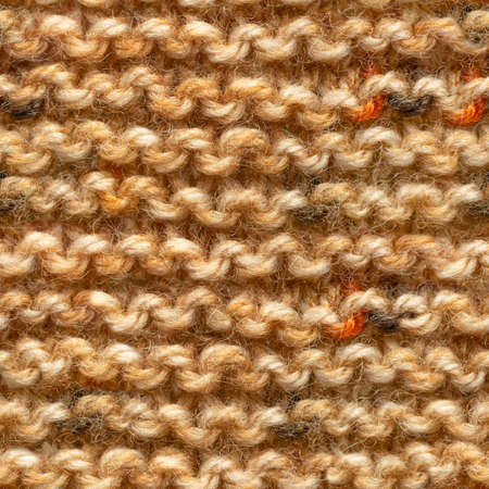 Brown yellow knitted fabric seamless pattern for borderless fill. Knitted fabric repeating pattern for background close up.