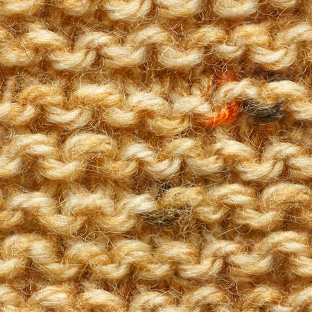 Brown yellow beige color knitted fabric seamless pattern for borderless fill. Knitted fabric repeating pattern for background close up.