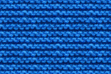 Blue Knitwear Fabric Texture. Machine Knitting Texture Macro Snapshot. Dark Blue Knitted Background.