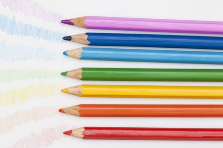 colored pencils laid out in order of rainbow colors on a white background