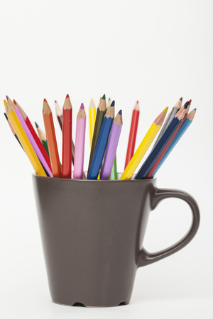 colored pencils in mug on white background Archivio Fotografico