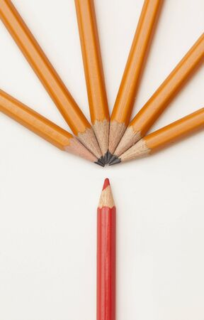 yellow pencils on white background and one red. The concept of differences
