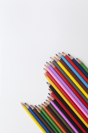 colored pencils laid out in the form of a wave on a white background