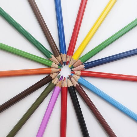 colored pencils laid out in a sun shape on a white background Archivio Fotografico