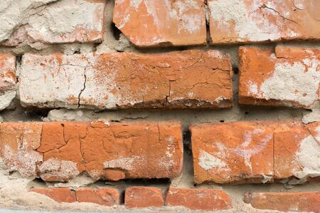 dilapidated wall: Masonry walls made of red bricks with traces of crumbling plaster