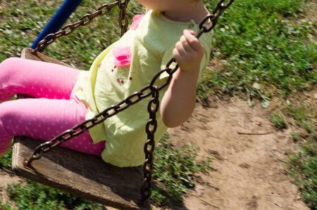 chain swing ride: Child swinging on a wooden swing in the yard