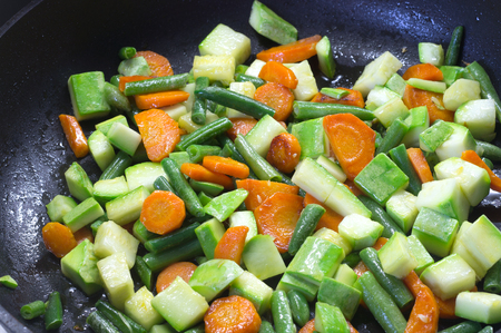 Sliced vegetables, fried in butter in a frying pan when cooking a side dish for dinner