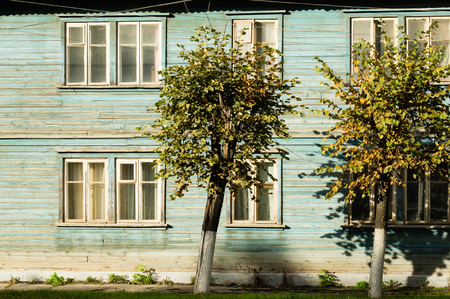 Trees on a background of a wooden house with blue dilapidated wall and double glazed windows. Stock Photo