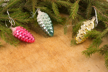 The branches of Christmas trees and  fallal cone decorations on the background of wooden boards. Christmas and New Years background.